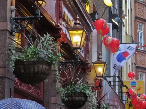 Flower baskets, lamps etc. above Waxy's Little Sister, on the corner of Wardour Street and Lisle Street...