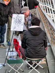 A caricaturist, plying his trade on Hungerford Bridge...