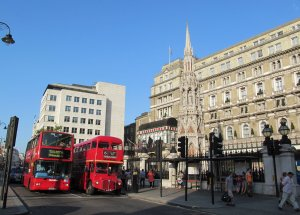 Two double-deckers, one old, one new, in front of Charing Cross Station...