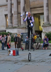 A juggling uni-cyclist , performing in front of the National Gallery...