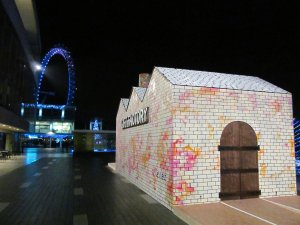 A temporary 'Gift Factory' outside the Royal Festival Hall on London's South Bank, with the London Eye visible in the distance...